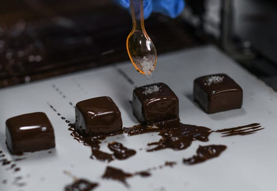 Park Lake Creamery co-owner and chocolatier Konstantin Zsigo adds a dash of sea salt to his handcrafted dark chocolate-covered caramels Wednesday, Dec. 4, 2019.