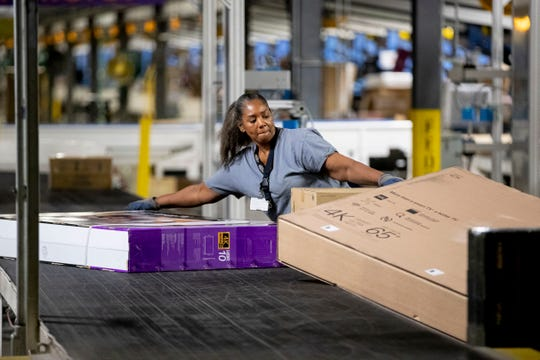 Sharon Short moves large packages onto a conveyor belt Wednesday, Dec. 4, 2019, at the FedEx Ground Olive Branch hub.