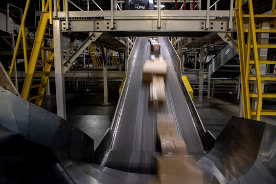 Packages move along a conveyor belt Wednesday, Dec. 4, 2019, at the FedEx Ground Olive Branch hub.