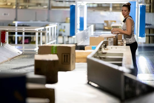 Hayley Winningham checks packages as they pass by her on a conveyor belt Wednesday, Dec. 4, 2019, at the FedEx Ground Olive Branch hub.