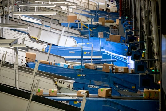 Packages ride conveyor belts into the FedEx Ground Olive Branch hub Wednesday, Dec. 4, 2019.