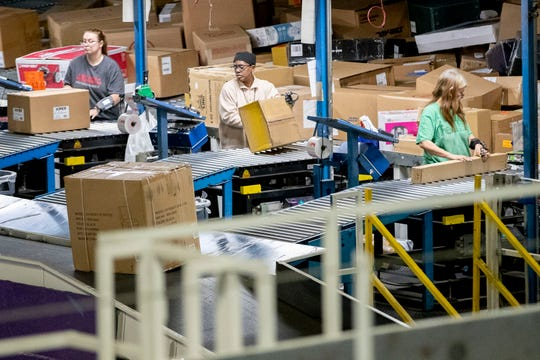 Employees sort packages Wednesday, Dec. 4, 2019, at the FedEx Ground Olive Branch hub.