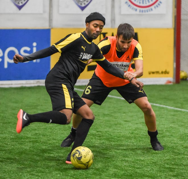 Forward/midfielder Max Ferdinand tries to work the ball past and defender Guilherme Veiga at Wave practice this week.