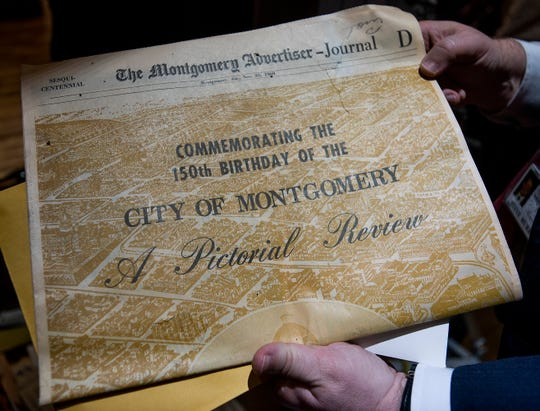 A Montgomery Advertiser Sesquicentennial Special Section is pulled from the time capsule, that was sealed during Montgomery's 150th anniversary in 1969 with instructions not to open it until the city's 200th anniversary, at City Hall in Montgomery, Ala., on Tuesday, December 3, 2019.