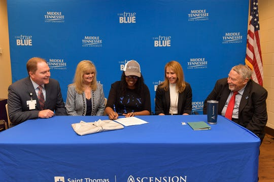 MTSU student veteran Martinna Young, center, signed an agreement making her the inaugural member of the Ascension Saint Thomas Nursing Corps, a partnership with MTSU that seeks to create a robust pipeline of strong registered nurse candidates who are also military veterans. Ascension Saint Thomas CEO and President Tim Adams, left, MTSU School of Nursing Director Jenny Sauls, Ascension Saint Thomas COO Michelle Robertson and MTSU College of Behavioral and Health Sciences Dean Terry Whiteside viewed the signing Tuesday, Nov. 26, in the Daniels Veterans Center on the MTSU campus.