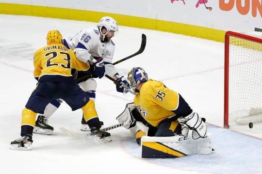 Tampa Bay Lightning right wing Nikita Kucherov (86), of Russia, scores the winning goal past Nashville Predators goaltender Pekka Rinne (35), of Finland, and Rocco Grimaldi (23) in overtime of an NHL hockey game Tuesday, Dec. 3, 2019, in Nashville, Tenn. The Lightning won 3-2.
