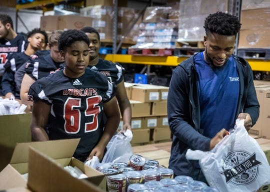 Kevin Byard of the Titans, right, volunteers with Overton High School football players at The Bridge Ministry on Dec. 3. Volunteering is a great way to connect with others while helping your community.