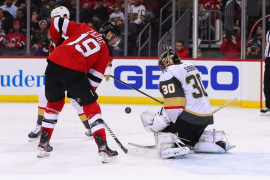 Vegas Golden Knights goaltender Malcolm Subban (30) makes a save while New Jersey Devils center Travis Zajac (19) looks for the rebound during the second period at Prudential Center.
