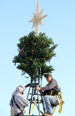 Luna County workers Roman Quarrell, left, and Ezra Uzueta began erecting the 30-foot tall Christmas Tree this week in preparation for the community tree lighting ceremony at 7 p.m. on Saturday in front of the historic courthouse lawn.