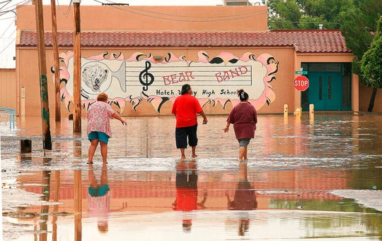 In this Aug. 16, 2006 file photo, Hatch, N.M., residents walk through floodwaters in their town. Federal and local officials are moving ahead with plans for a $12.7 million earthen dam to protect a southern New Mexico village from flooding. The project in Hatch, a farming community made famous for its crops of chile peppers, comes as a number of other dams in New Mexico are classified as being in poor shape.