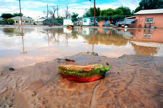 This Aug. 16, 2006 file photo shows a Hatch chili that is changing from green to red after being picked resting on an old foundation near a church after flooding in Hatch, N.M. Federal and local officials are moving ahead with plans for a $12.7 million earthen dam to protect a southern New Mexico village from flooding. The project in Hatch, a farming community made famous for its crops of chile peppers, comes as a number of other dams in New Mexico are classified as being in poor shape.