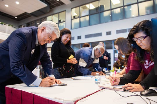 New Mexico State University Chancellor Dan Arvizu writes a check Dec. 3, 2019, during NMSU's Giving Tuesday event in Corbett Center Student Union.