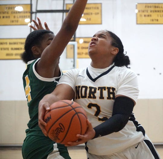 North Farmington Raider Maya Kelly tries to get a shot up to the hoop past Groves' Kaitlyn Quinn, left.