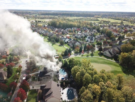 Smoke billows from a Canton Township house fire on Oct. 23, 2018. Over a year later the remains of the seriously-damaged home still remained at the site.