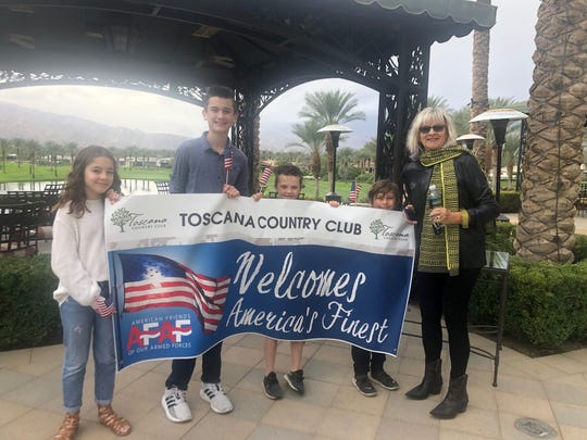 """A host family awaits their """"adoptees"""" with a welcome sign."""