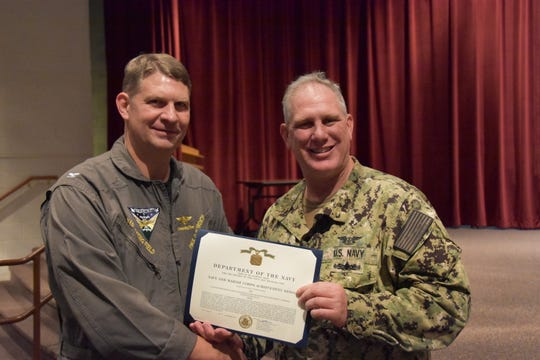 Capt. Paul Bowdich, Whiting Field commanding officer, presents Chief Aviation Boatswains Mate Shane Ammons with a Navy and Marine Corps Achievement Medal for his actions saving a life in Milton Oct. 30.