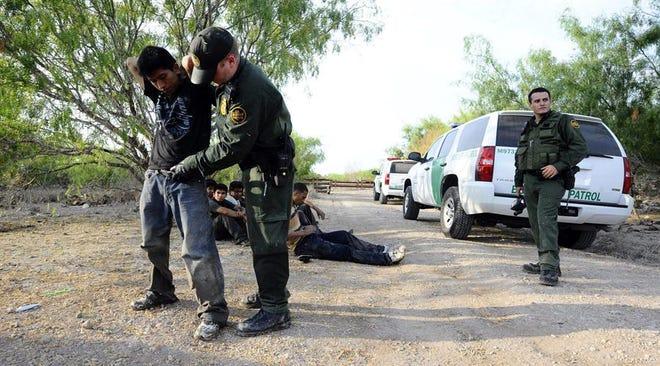 Miembros de la Patrulla Fronteriza de Estados Unidos requisan a una persona detenida.