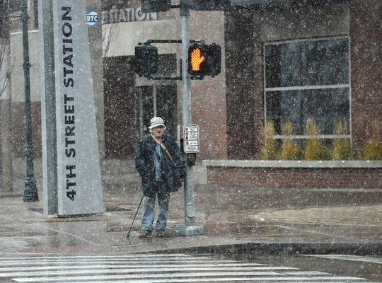 A file photo of a pedestrian crossing a crosswalk in snowfall.