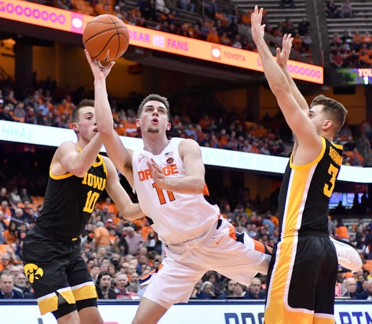 Dec 3, 2019; Syracuse, NY, USA; Syracuse Orange guard Joseph Girard III (11) puts up a shot as Iowa Hawkeyes guard Joe Wieskamp (10) and guard Connor McCaffery (30) defend in the second half at the Carrier Dome.