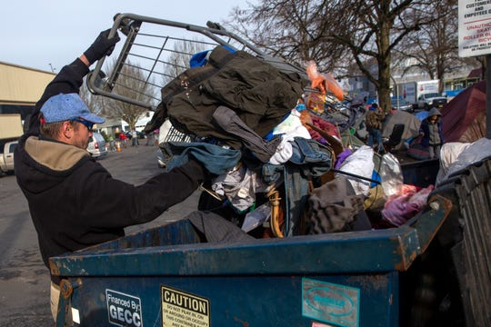 Anthony Stevens, who has been living in front of ARCHES for a few weeks, throws trash cleared from the camp into a dumpster on Commercial Street in Salem on Dec. 4.