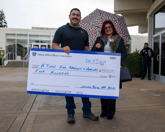 Ruben Sanchez, left, is photographed next  Debbie Aguilar founder of A Time of Grieving and Healing as they both hold a giant check of $500 dollars during the Salinas Police Officers Association kick off fundraiser on on Dec. 04, 2019.