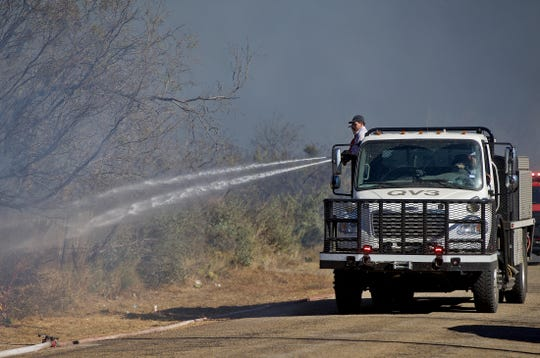 Firefighters with the Quail Valley Volunteer Fire Department douse a hotspot on a fire burning on Bristow Road northeast of San . Angelo on Tuesday, Dec. 3, 2019.