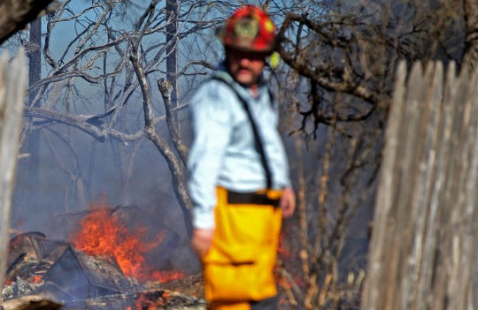 A firefighter monitors a blaze on Bristow Road northeast of San Angelo that broke out around 1 p.m. Tuesday, Dec. 3, 2019.