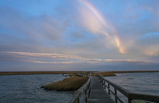 A cold front moves through Tangier Sound at sunrise, producing a rainbow over the boardwalk at Fox Island.