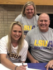 Calvary's Brylee Kelley signs with LSUA as her parents look on Tuesday.