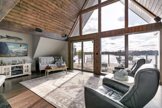 The living room has a soaringvaulted ceiling and full A-frame picture windows that spanfloor-to-ceiling and wall-to-wall, providing uninterrupted views of the lake.