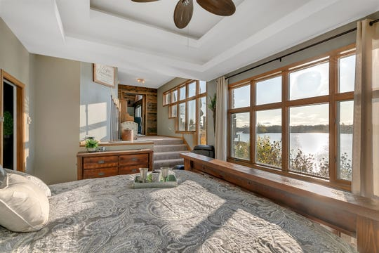One wall of the master suite is filled with lakefront windows and stairs lead down to the main sleeping area.