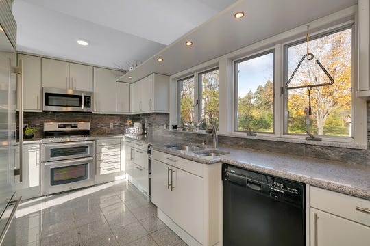 The kitchen offers a Sub-Zero refrigerator, granite countertops and floor and plenty of cabinetry and storage space.