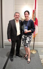Todd DeAngelis, president of the Florida Municipal Communicators Association, presents one of three awards to the city to Lizzy Kelly, marketing and public information manager for the city of Tallahassee. The city was honored during the association's annual conference.