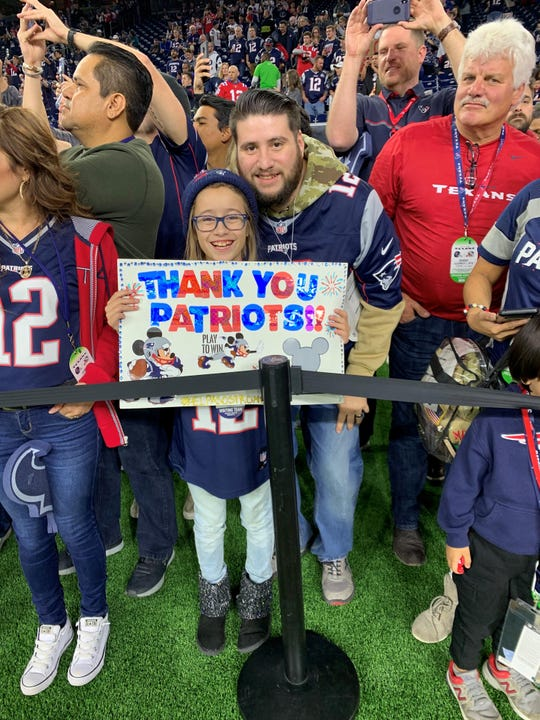 Kaitlyn Melendez, 9, with her dad Raul Melendez holds up a sign thanking the Patriots for being able to attend the Dec. 1 game in Houston.