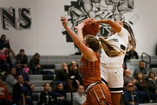 Horizon's Artyana Diggs attempts to take a shot against Riverside's Charlize Bustillos during the game Tuesday, Dec. 3, at Horizon High School.