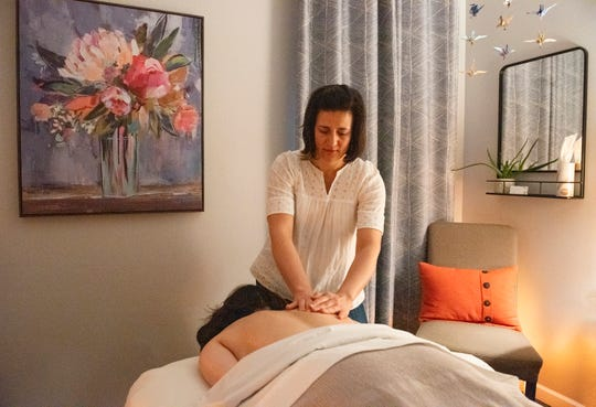 Message therapist Nadine Jacobs Gammon massages a patient at her location in Greenville.