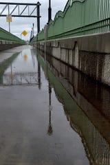 Raindrops splash into a puddle on the Highway 101-Santa Clara River bridge on Dec. 4, 2019.