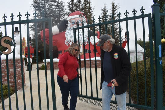 Mike Barber and Mary Anne Rooney lock the gate housing the huge freeway Santa Claus.