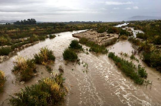 Water flows through the Santa Clara River beneath Highway 101 on Dec. 4, 2019, as rain falls on Ventura County.