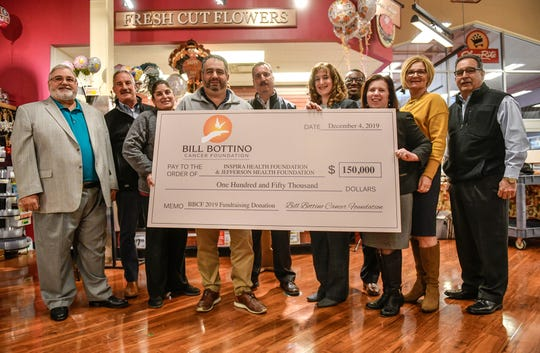 Members of the Bill Bottino Cancer Foundation present a check for $150,000 to Inspira Health Foundation and Kennedy Health Foundation's Sidney Kimmel Cancer Care at Washington Township representatives during a ceremony held Wednesday, Dec. 4, 2019 at the Bottino's ShopRite store of Vineland.