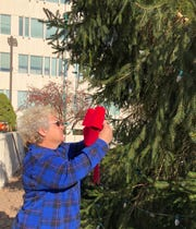 Diane Starn, who donated her evergreen to the city, places the first red bow on what is now the city's Christmas tree.