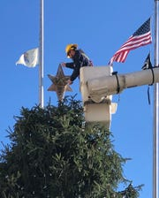 Jason Garrison of Vineland Electric Utility places star atop of Vineland Christmas tree at City Hall.