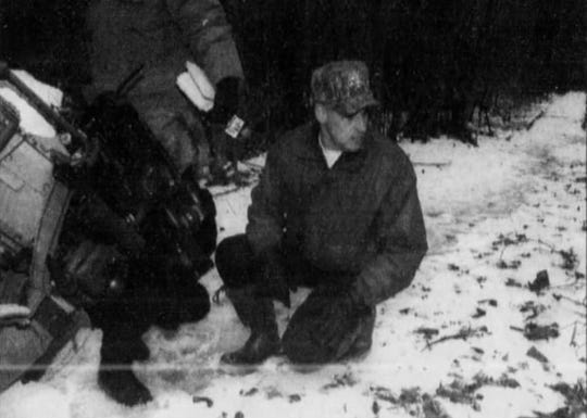New Castle County Police Cpl. Butch Lefebvre examines cougar tracks in 1996. Lefebvre led an effort to catch cougars.