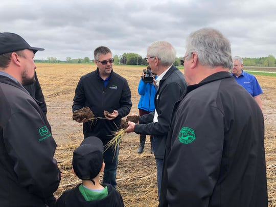 Nick Guilette, center, discusses soil health principles with Wisconsin Governor, Tony Evers, at a demonstration farm field day.