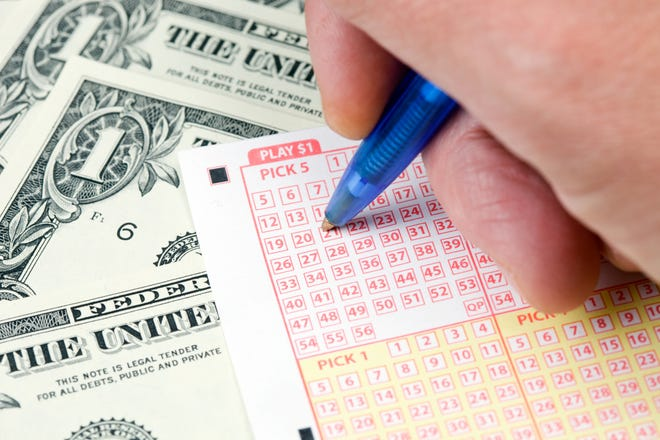 A male hand is using a pen to mark lottery numbers on a ticket resting on a background of one dollar bills.A related image from my portfolio:aA
