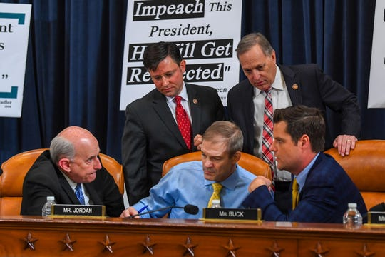From lower left, Rep. Louie Gohmert, R-Texas; Rep. Jim Jordan, R-Ohio; Rep. Matt Gaetz, R-Fla. and from left top, Rep. Mike Johnson, R-La., and Rep. Andy Biggs, R-Ariz., huddle during a break of the House Judiciary Committee impeachment inquiry hearing on President Donald Trump, Dec. 4, 2019.