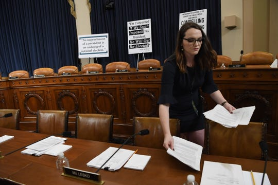 A congressional staff member distributes documents on Dec. 4, 2019, before the House Judiciary Committee holds the first formal impeachment inquiry of President Donald Trump to explore how the Constitution applies to allegations of misconduct.