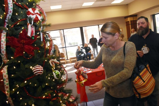 Christine (left) and Chad Bordelon hang an ornament on the Tree of Life in memory of their late son, Eric.
