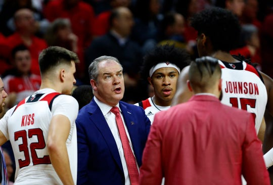 Rutgers Scarlet Knights head coach Steve Pikiell talks to guard Peter Kiss (32) and center Myles Johnson (15) last March.