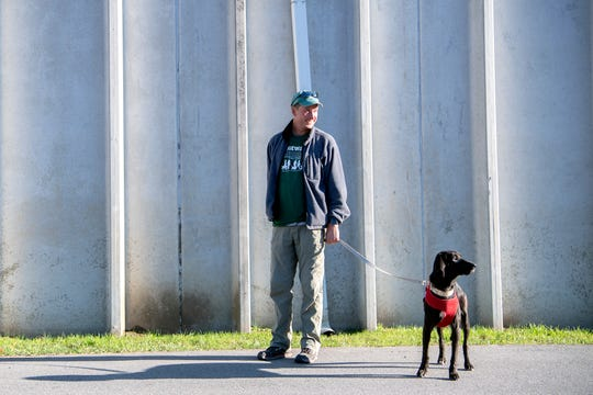 Volunteer Paul Kersch and dog Brooks stop to look for the source of a noise as they go for a walk around Brother Wolf Animal Rescue on Dec. 4, 2019.